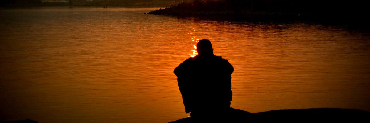 Man mourning at lake